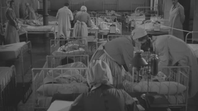 stockvideo's en b-roll-footage met ms doctors and nurses attending to patients in beds at hospital room - ziekenzaal