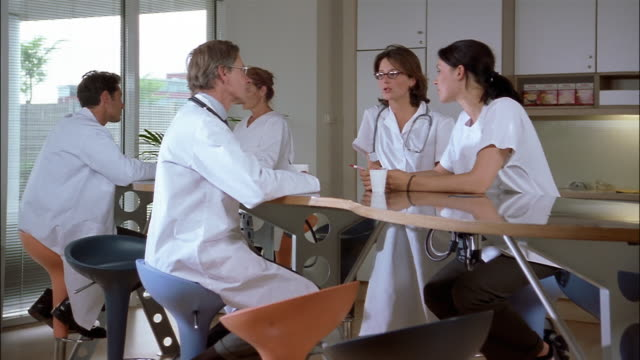 Doctors and nurses, in white lab coats and scrubs, hold coffee cups and talk at a cafeteria table.
