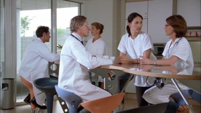 doctors and nurses, in white lab coats and scrubs, hold coffee cups and talk at a cafeteria table. - laborkittel stock-videos und b-roll-filmmaterial