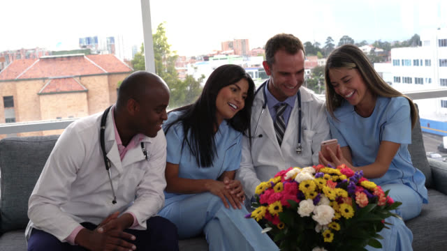 doctors and nurses taking a break watching a video - scrubs stock videos & royalty-free footage