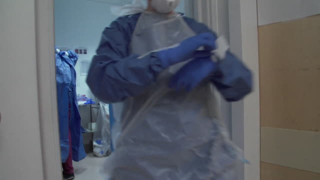 vídeos y material grabado en eventos de stock de doctors and nurses treating coronavirus patients in intensive care unit at university college hospital, london, putting on ppe to protect themselves - vestimenta de hospital