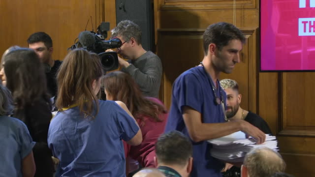 doctors and nurses wearing scrubs hand out document at labour press conference that labour says proves the nhs has been part of trade talks between... - scrubs stock videos & royalty-free footage