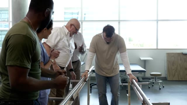doctors and patients cheer as a man uses parallel bars to walk after debilitating injury - conquering adversity stock videos & royalty-free footage