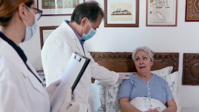 doctors and senior woman - bedclothes stock videos & royalty-free footage