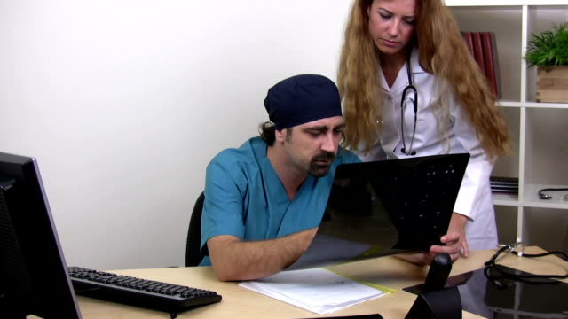 doctors are looks at x-rays - doctor multitasking stock videos & royalty-free footage