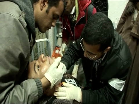 doctors at a makeshift hospital attend to a protester shot in the neck during an antigovernment demonstrations cairo - makeshift stock videos & royalty-free footage