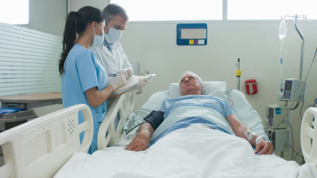 doctors checking on patient at the icu - casualty stock videos & royalty-free footage