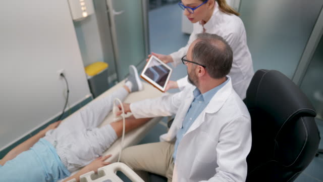 doctors consulting during ultrasound diagnose - injured stock videos & royalty-free footage