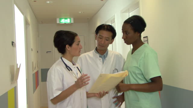 ms doctors discussing file standing in hospital corridor / helmond, north brabant, netherlands - 男性と複数の女性点の映像素材/bロール