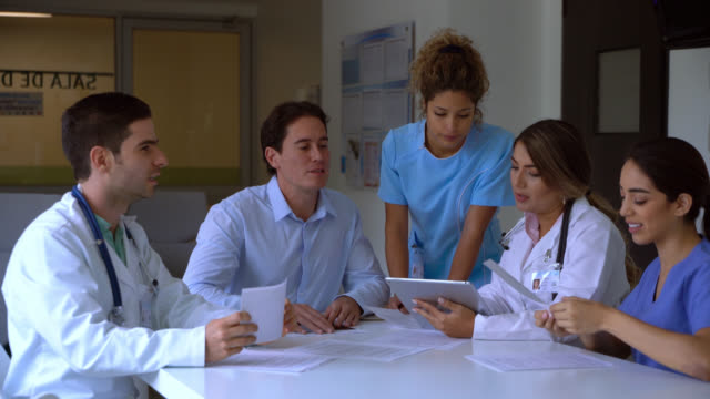 doctors during a medical board looking at documents and tablet and then handshaking - staff meeting stock videos & royalty-free footage
