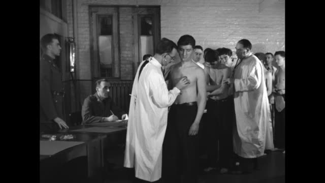 WS doctors examine shirtless men as others wait their turn as part of enrollment into the Civilian Conservation Corps' Forest Army / SOT doctor uses...