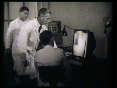 vídeos y material grabado en eventos de stock de doctors examining pointing talking xray of chest cavity mcu xray of chest xradiation xray hospital medical - 1952