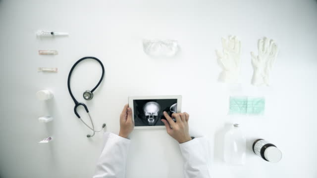 Doctors Examining X-Ray Image On A Tablet