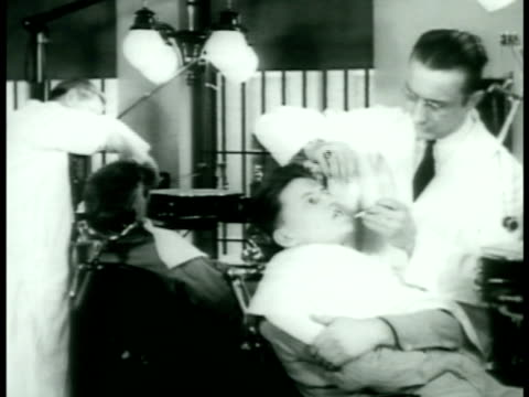 doctors examining young male w/ stethoscope. two dentist examining young men making impressions. prisoner seated before prison board. - ドキュメンタリー映画点の映像素材/bロール