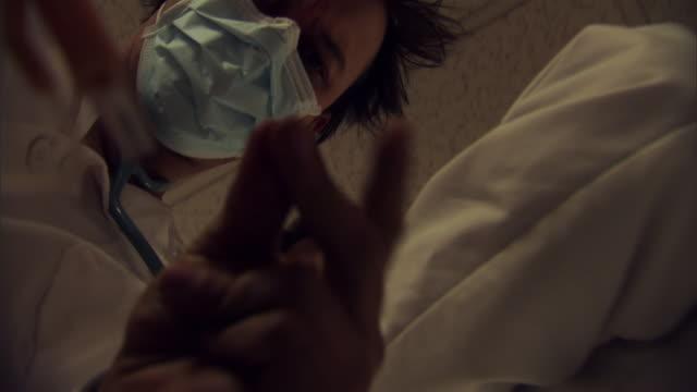 POV CU LA Doctors flicking fingers, putting on oxygen mask as they move hospital gurney through corridor / Burlington, Vermont, USA