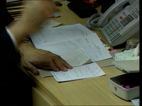 GPs Strike Action LIB GP examining woman patient in consulting room CMS Doctor's hands as writing at desk CMS Doctor's hands as opening mail TBV...