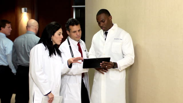 doctors have discussion interacting with digital tablet - ws - hospital leadership stock videos & royalty-free footage