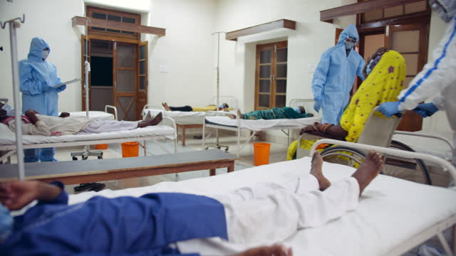 vídeos de stock e filmes b-roll de doctors helping aged senior old women in wheelchair across a ward of patients lying on bed in a coronavirus hospital ward tested positive for covid-19 virus - ala hospitalar