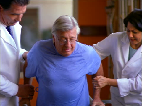 2 doctors helping senior male patient in hospital gown walk slowly in rehab / physical therapy - femmina con gruppo di maschi video stock e b–roll