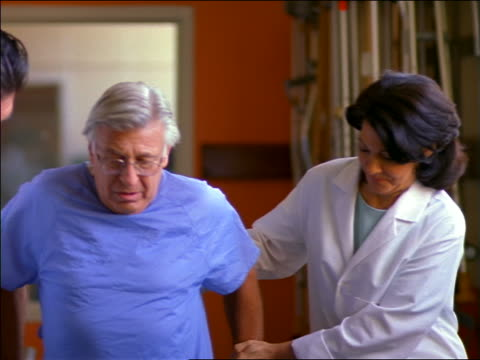 2 doctors helping senior male patient in hospital gown walk slowly in rehab / physical therapy