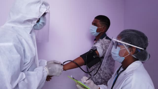 doctors in full protective gear and body suit examine a patient's blood pressure as they wwork in a team during the global coronavirus pandemic where everyone is extra careful - full suit stock videos & royalty-free footage