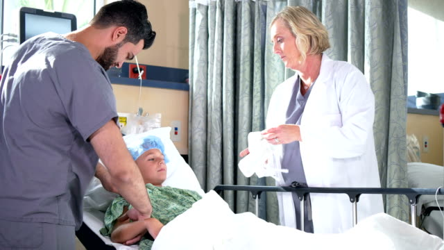 doctors in hospital prepping boy for medical procedure - lying on back stock videos & royalty-free footage