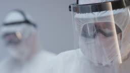 Doctors in Protective Suits Applying Oximeter on Coronavirus Patient's Finger - Close Up Slow Motion Tilting Shot