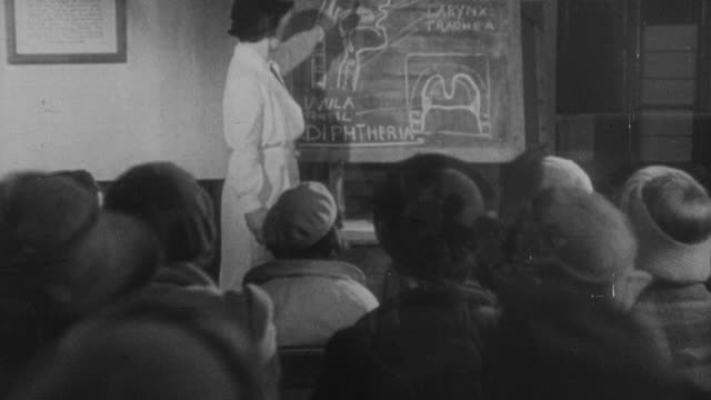 1941 montage doctors informing parents about the dangers of diphtheria / united kingdom - diphtherie stock-videos und b-roll-filmmaterial