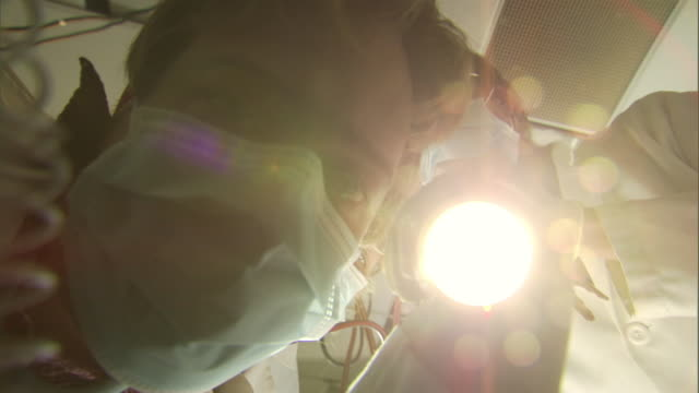 ms cu la pov doctors leaning over camera in operating room, holding flashlight, jumper cables, syringes and pliers / burlington, vermont, usa - 10 seconds or greater stock videos & royalty-free footage