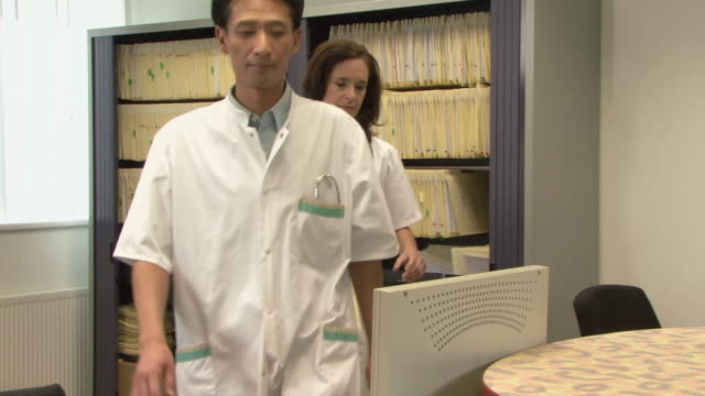 ms doctors looking at file in medical office / helmond, north brabant, netherlands - ナースステーション点の映像素材/bロール
