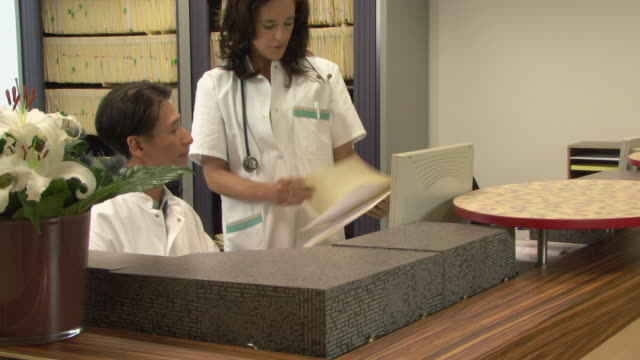 ms zi doctors looking at files in medical office / helmond, north brabant, netherlands - ナースステーション点の映像素材/bロール