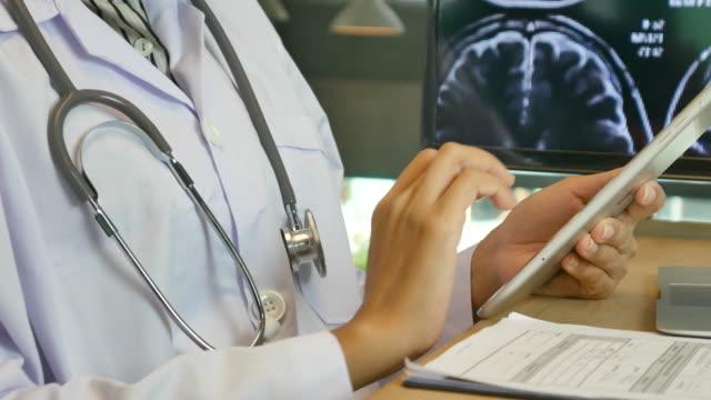 vídeos de stock e filmes b-roll de doctors looking mri scans on digital tablet pc - bata cirúrgica