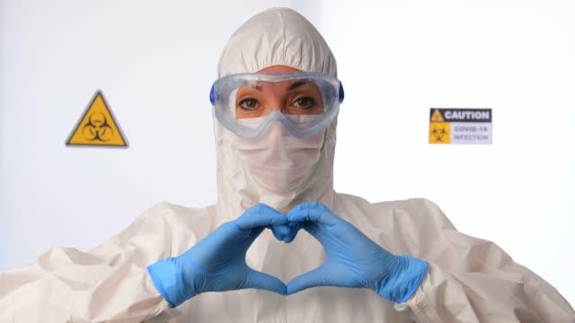 コロナウイルスcovid 19新しいコロナウイルスの流行の間に心臓の形を作り、愛を送る医師 - クリーンスーツ点の映像素材/bロール