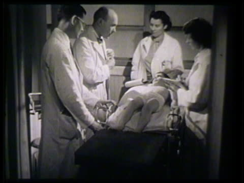 vídeos y material grabado en eventos de stock de doctors & nurses around young boy, topless, lying on hospital bed, doctor w/ flashlight & tongue depressor to check boy's mouth & throat. - 1952