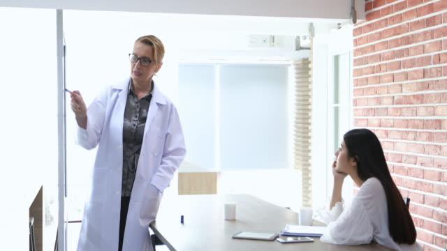 vídeos de stock, filmes e b-roll de médicos ou cientistas estão ensinando e explicando os alunos e pacientes, escrevendo a bordo - jaleco de laboratório