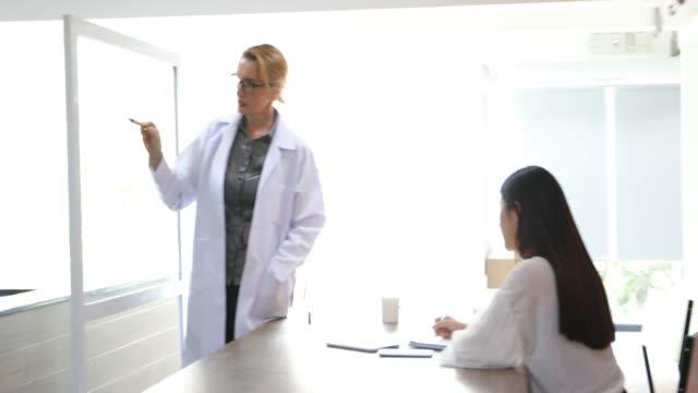 vídeos de stock, filmes e b-roll de os doutores ou os cientistas estão ensinando e explicando estudantes e pacientes que escrevem a bordo - jaleco de laboratório