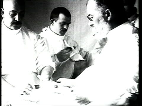 1915 b/w ms doctors performing surgery on wounded soldier/ russia - prima guerra mondiale video stock e b–roll