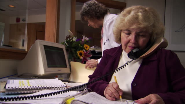 ms doctor's receptionist answering on telephone, woman placing file in background / burlington, vermont, usa - doctor multitasking stock videos & royalty-free footage