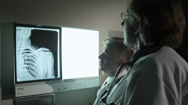 Doctors referencing a patient's x-ray.