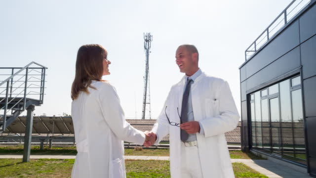 MS doctors shaking hands outdoors
