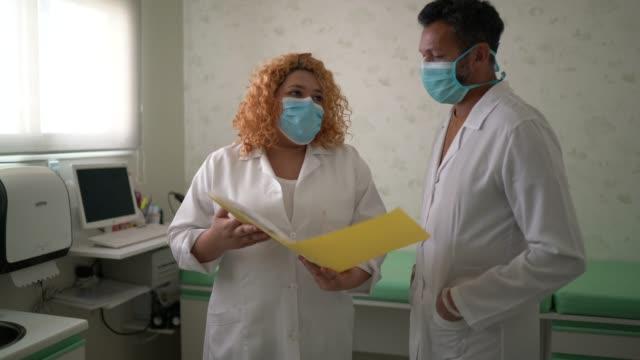 ärzte teilen informationen über eine krankenakte mit gesichtsmaske - klemmbrett stock-videos und b-roll-filmmaterial