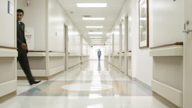WS POV Doctors talking and walking in hall / Houston, Texas, United States