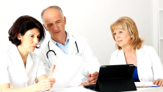 vidéos et rushes de équipe de médecins examinant un document - trois personnes