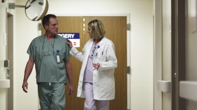 WS MS Doctors walking in hospital corridor and talking / Payson, Utah, USA