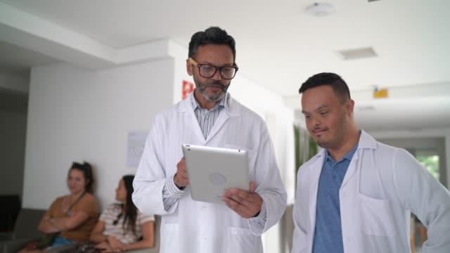stockvideo's en b-roll-footage met artsen (met inbegrip van speciale behoeftenjongen) die gebruikend digitale tablet bij het ziekenhuis lopen - minder validen