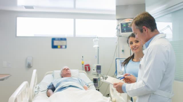 doctors working at the icu - reparto di terapia intensiva video stock e b–roll