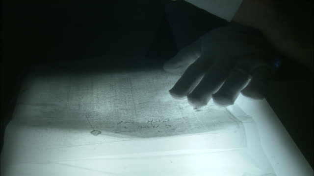 a document is viewed under a magnifying glass. - lupe stock-videos und b-roll-filmmaterial