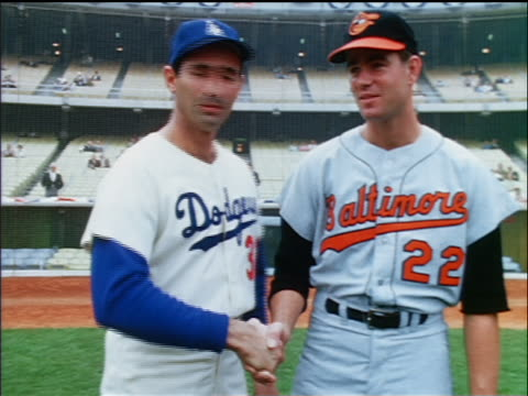Dodger Sandy Koufax Oriole Jim Palmer holding hands posing on field / industrial