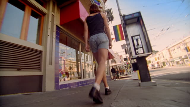 vídeos de stock e filmes b-roll de dog point of view following behind woman walking down sidewalk in castro district of san francisco, california - seguir atividade móvel