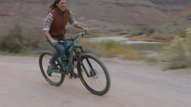 vídeos de stock, filmes e b-roll de dog runs to catch up as young woman rides mountain bike up dirt road. - trilho para bicicleta esporte ao ar livre